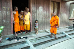 Flicka och buddistiska munkar Arkivfoto