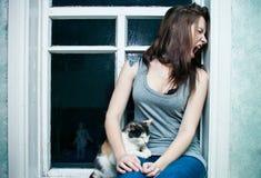 Flicka och en katt på fönstret Arkivbild