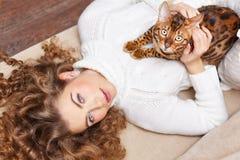 Flicka och en katt som ligger på soffan Fotografering för Bildbyråer