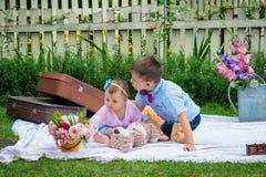 Flicka och en pojke i trädgård royaltyfri fotografi