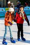flicka och en pojkevän på isbanan Royaltyfri Foto