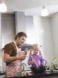 Flicka och fader Baking In Kitchen royaltyfria bilder