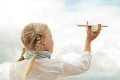 Flicka- och flygplanleksak på den molniga himlen Royaltyfria Bilder
