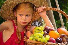 Flicka- och fruktkorg arkivfoton