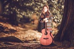 Flicka och gitarr i parkera Fotografering för Bildbyråer