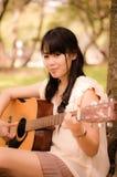 Flicka och gitarren Arkivbild