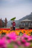 Flicka och golden retriever i blommorna Arkivfoto