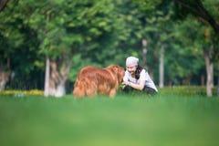 Flicka och golden retriever som spelar i gräset royaltyfri bild