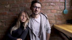 Flicka och grabb i ett kafé nära posera för tegelstenvägg De ler, ser de De är lyckliga stock video