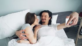 Flicka och grabb som tar selfie i säng med smartphonekameran som kysser att krama arkivfilmer
