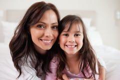 Flicka och henne moder som ligger på ett underlag Arkivbild