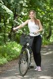 Flicka och hennes cykel Arkivbild