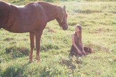 Flicka och hennes häst på det solbelysta fältet royaltyfri bild
