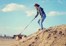 Flicka och hennes hund i stranden Arkivfoto