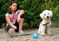 Flicka och hennes hund i trädgården