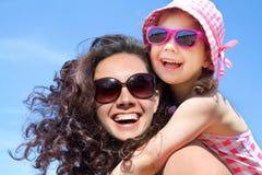 Flicka och hennes moder på sjösidan Royaltyfria Bilder
