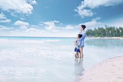 Flicka och hennes moderanseende på kusten Arkivfoton