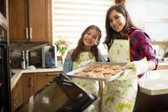 Flicka och hennes stekheta kakor för mamma tillsammans Arkivfoto