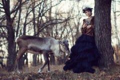 Flicka och hjortar i skogen Arkivfoton