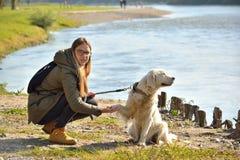 Flicka och hund, i att huka sig ned position arkivfoton