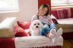Flicka och hund på en soffa royaltyfria bilder