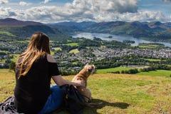 Flicka och hund som stirrar på Keswick och Derwent vatten, Cumbria royaltyfria foton