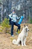 Flicka och hund som trekking i skogen Arkivbilder