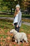 Flicka- och hundanseende i höstsidor Royaltyfri Bild