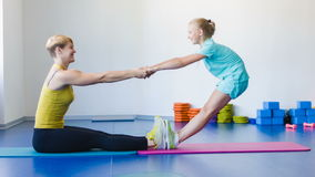 Flicka och instruktör eller moder som gör gymnastiska övningar i konditiongrupp lager videofilmer