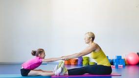 Flicka och instruktör eller moder som gör gymnastiska övningar i konditiongrupp arkivfilmer