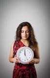 Flicka och klocka Arkivbild