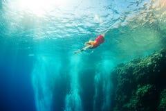 Flicka och koraller i havet arkivfoton