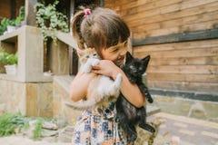 Flicka och kvinna som spelar med kattungar royaltyfri bild