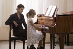 Flicka och lärare Playing Piano Arkivbild