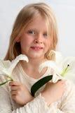 Flicka och liljar arkivbild