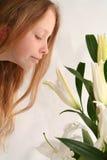 Flicka och liljar arkivfoto