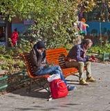 Flicka och män som sitter med mobilen Fotografering för Bildbyråer