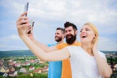 Flicka och man med mobil smartphoneskommunikation direktanslutet Selfie Tid Liv direktanslutet Folk som tar selfie eller trycknin royaltyfria foton