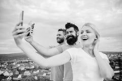 Flicka och man med mobil smartphoneskommunikation direktanslutet Selfie Tid Liv direktanslutet Folk som tar selfie eller trycknin arkivbild