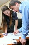 Flicka- och manarbete i kontoret Royaltyfri Fotografi