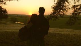 Flicka- och manloppet, går i skog, tycker om landskapet på solnedgången Vänhandelsresande reser med ryggsäckar lycklig familj arkivfilmer