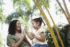 Flicka och moder som spelar Patty Cake In Park Royaltyfria Bilder