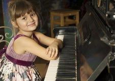 Flicka och piano royaltyfria foton