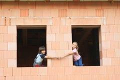 Flicka och pojke i fönstren Fotografering för Bildbyråer