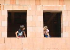 Flicka och pojke i fönstren Royaltyfri Fotografi
