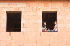 Flicka och pojke i fönstret Arkivfoto