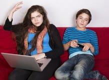 Flicka och pojke med bärbara datorn och telefonen Fotografering för Bildbyråer