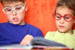 Flicka och pojke med exponeringsglasläsning en boka Fotografering för Bildbyråer