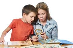 Flicka och pojke med förstoringsapparaten som ser hans isolat för stämpelsamling Arkivfoton