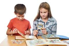 Flicka och pojke med förstoringsapparaten som ser hans isolat för stämpelsamling Royaltyfria Bilder